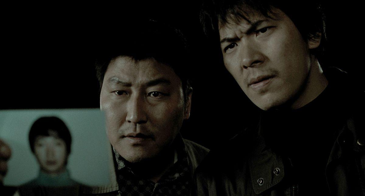 El detective Park (Song Kang-ho) y Seo (Kim Sang-kyung) sostienen la foto del sospechoso de asesinato Park Hyeon-gyu (Park Hae-il) en Memories of Murder
