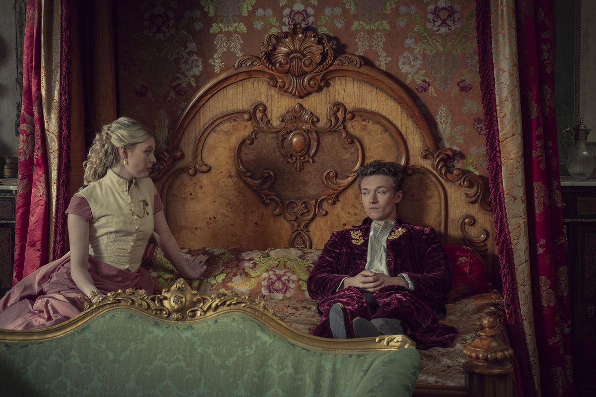 El príncipe Leopold se sienta completamente vestido y contemplativo en su cama en Les Irréguliers.