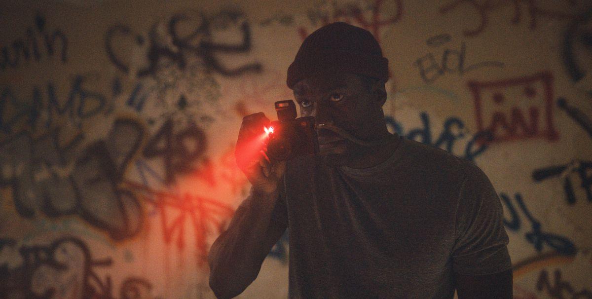 Yahya Abdul-Mateen II de pie en una habitación oscura, apuntando con la cámara al graffiti en Candyman 2021