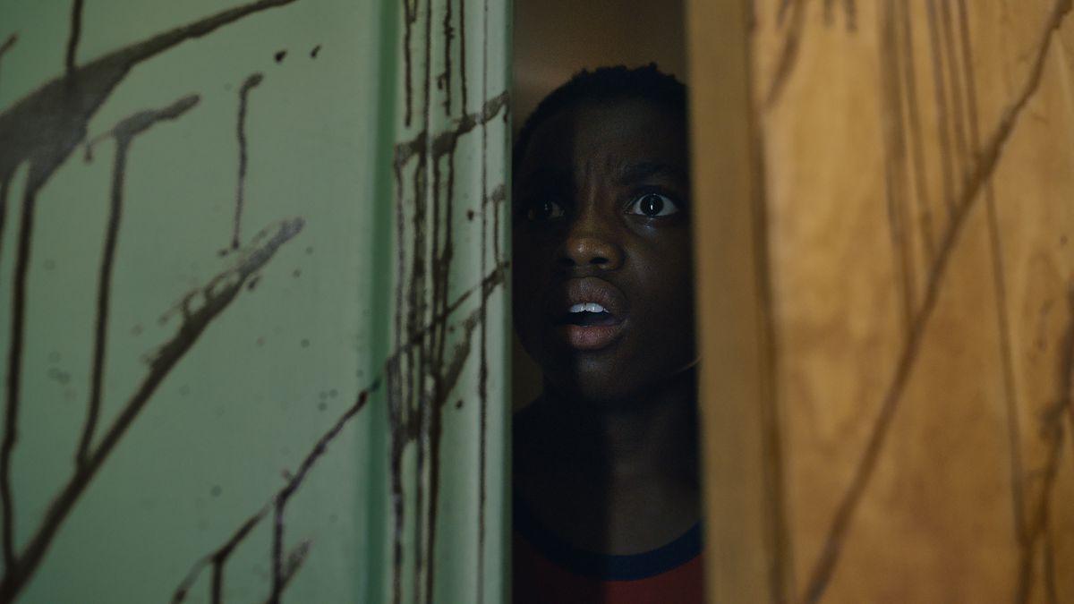 Horrorizado joven testigo negro se asoma a través de la puerta a una habitación salpicada de sangre en Candyman 2021