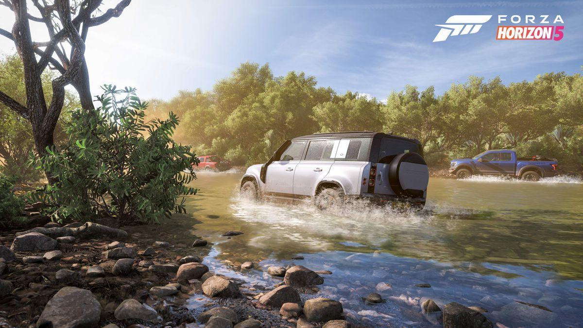 El vehículo utilitario deportivo y la furgoneta están compitiendo en un arroyo muy poco profundo.