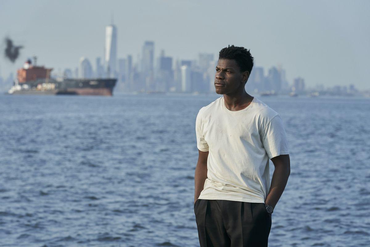 John Boyega, con una camiseta blanca y pantalones negros holgados, se para junto al agua con Manhattan de fondo en Naked Singularity.