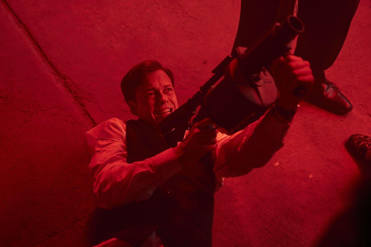 Un hombre de espaldas en un espacio iluminado en rojo, haciendo muecas y apuntando un enorme arma de proyectil hacia el cielo en Singularidad desnuda.