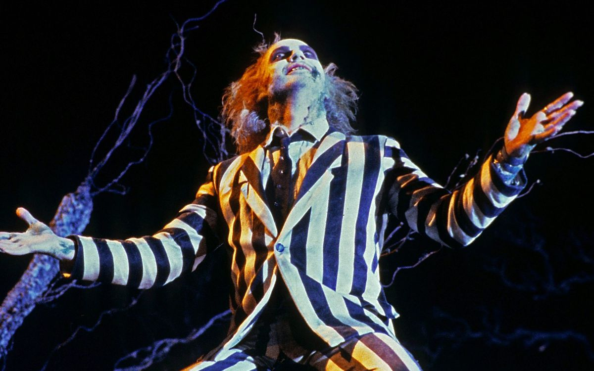 Michael Keaton as Beetlejuice with his arms outstretched