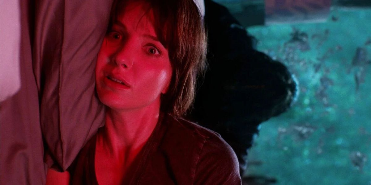 sideways shot of Annabelle Wallis as Madison lit in red as a mysterious shadow hovers over her bed in Malignant