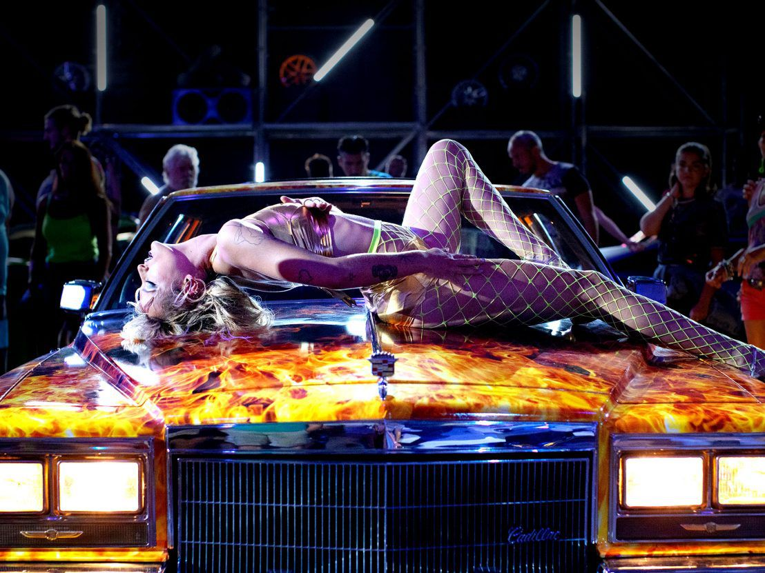 A young woman straddles atop a neon-painted car hood in Titane